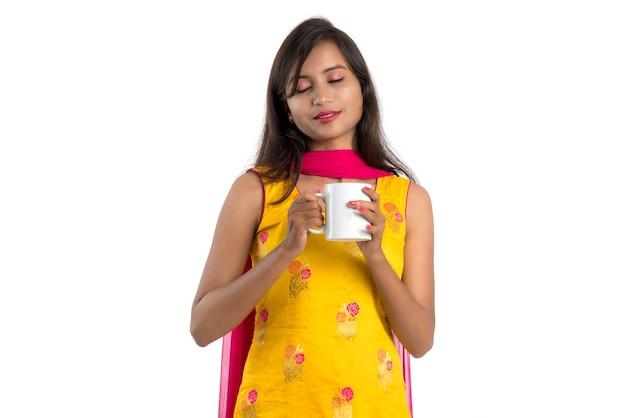 Hübsches junges mädchen mit tasse tee oder kaffee, die auf weiß aufwirft