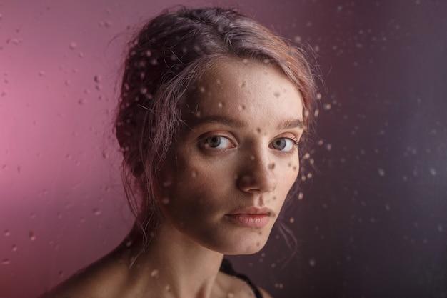 Hübsches junges mädchen untersucht kamera auf lila hintergrund. verschwommene wassertropfen rinnen über das glas vor ihrem gesicht