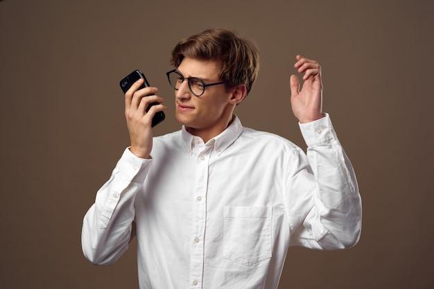 Hübsches junges männliches modell in einem stilvollen anzug, der im studio aufwirft