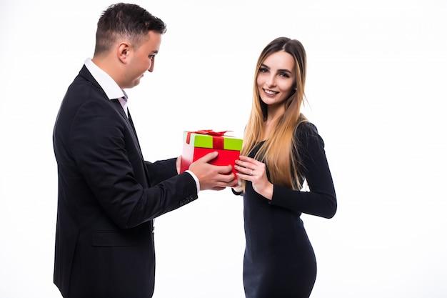 Hübsches junges mann- und mädchenpaar präsentieren geschenk in der roten schachtel auf weiß