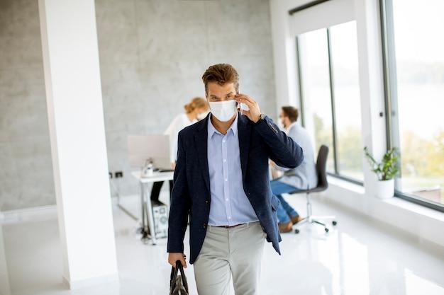 Hübsches junges mannpaar, das geht und handy benutzt, während schutzmasken tragen, um corona viruus in büroräumen zu verhindern