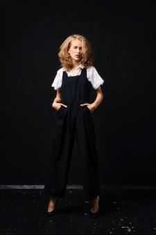 Hübsches junges model im schwarzen hosenanzug und im weißen hemd, die über schwarz aufwerfen