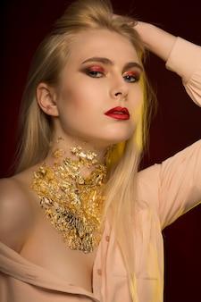 Hübsches junges model mit langen blonden haaren und goldenen folienmustern auf ihrer haut, das auf schwarzem hintergrund posiert