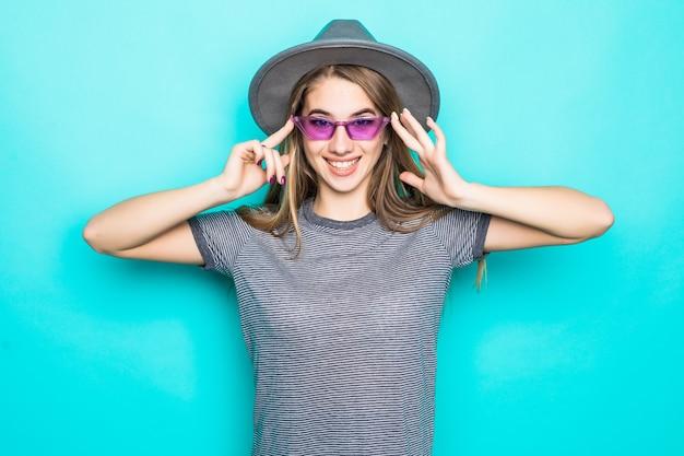 Hübsches junges modell im mode-t-shirt, im hut und in den blauen gläsern lokalisiert auf grünem hintergrund