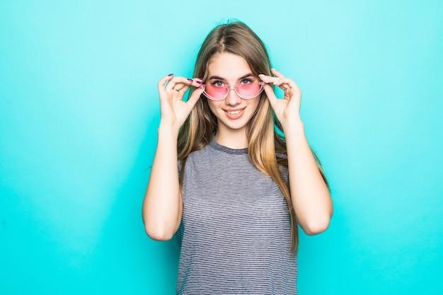 Hübsches junges modell im mode-t-shirt, im hut und in der transparenten brille lokalisiert auf grünem hintergrund