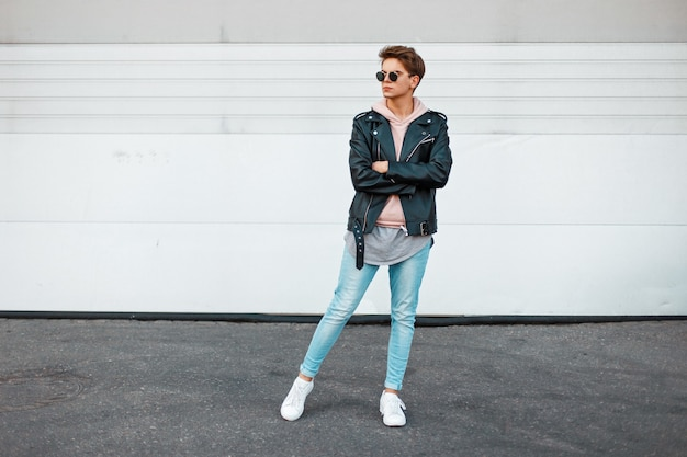 Hübsches junges modell mit einer frisur in modischer, trendiger markenkleidung in der nähe des weißen metalltors