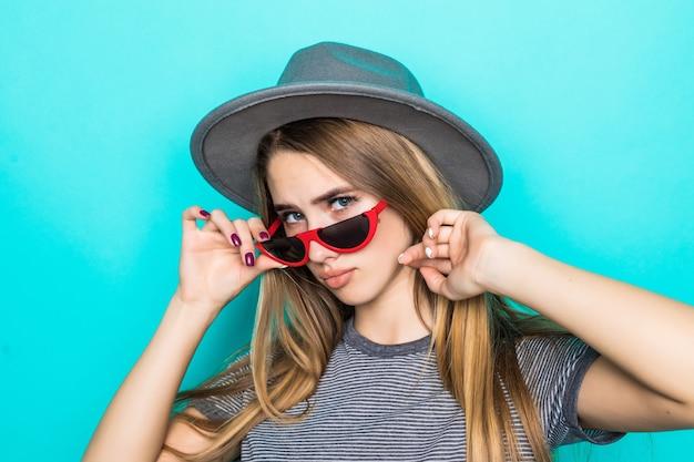 Hübsches junges modell mit goldhaar im mode-t-shirt, im hut und in der transparenten brille lokalisiert auf grünem hintergrund