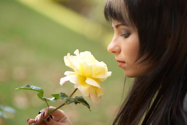 Hübsches junges outdoor-porträt mit gelber blumenrose