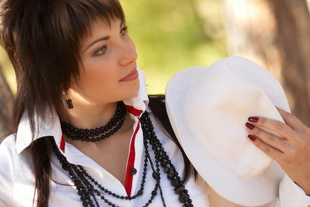Hübsches junges outdoor-porträt mit weißem hut