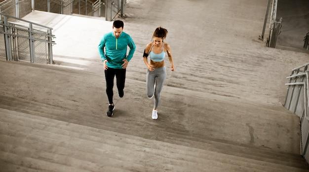 Hübsches junges paar, das in der städtischen umgebung läuft