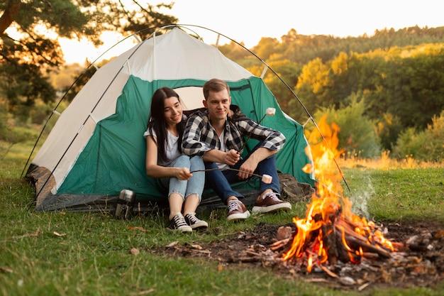 Hübsches junges paar, das lagerfeuer genießt