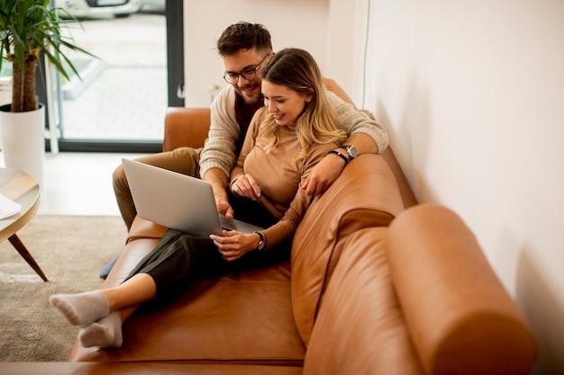 Hübsches junges paar, das laptop zusammen beim sitzen auf sofa zu hause verwendet
