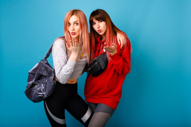 Hübsches junges paar der besten freundinnen, die luftküsse senden, fitness-sportkleidung und -taschen tragen, gesunden lebensstil, blaue wand.