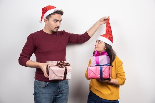 Hübsches junges paar von neujahrsmann und -frau in weihnachtsmützen, die weihnachtsgeschenkbox halten.