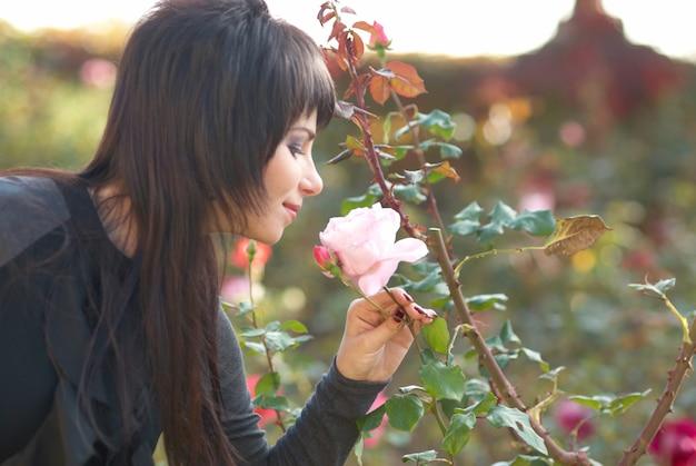 Hübsches junges porträt im freien mit rosa blumenrose im park