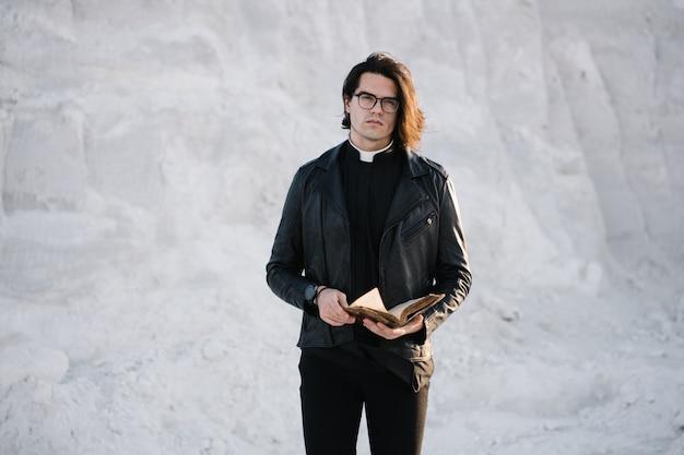 Hübsches junges priesterporträt draußen bei sonnenuntergang. er trägt eine brille, ein hemd mit römischem kragen und eine lederjacke.