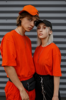 Hübsches junges stilvolles mädchen mit einem modischen gutaussehenden mann in orangefarbenen kleidern mit kappen stehen nahe der metallwand