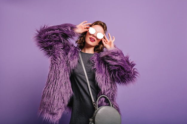 Hübsches junges weibliches modell, das in funkelnder sonnenbrille aufwirft und sanft lächelt