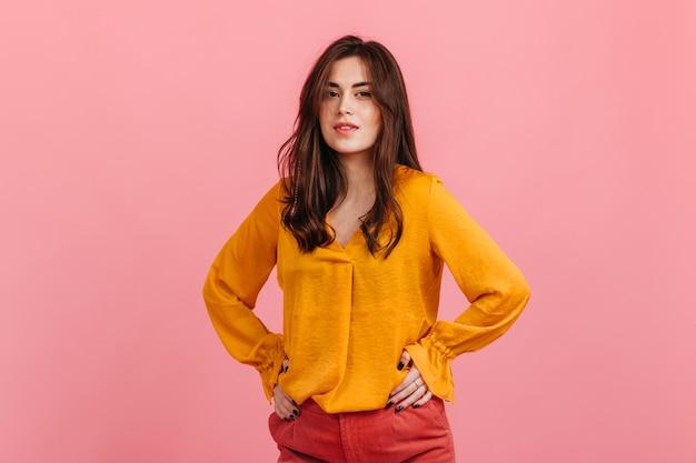 Hübsches junges weibliches modell mit braunen augen im leuchtend gelben hemd, das auf rosa wand aufwirft.