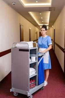 Hübsches junges zimmermädchen in uniform, das in einem langen korridor steht und saubere handtücher und andere sachen in hotelzimmern bekommt