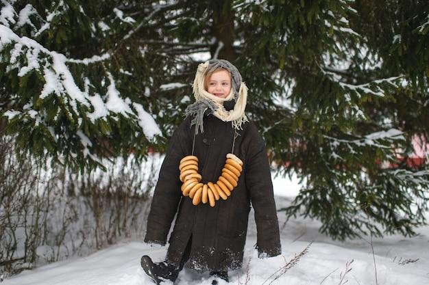 Hübsches kaukasisches dorfmädchen steht im schneewald