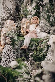 Hübsches kaukasisches kind mit langen blonden haaren lächelt und sitzt in der weihnachtsatmosphäre mit vielen geschmückten bäumen um sie herum und einem kleinen kaninchen