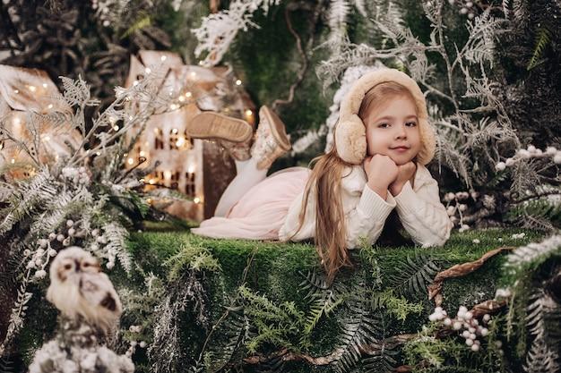 Hübsches kaukasisches kind mit langen blonden haaren liegt in der weihnachtsatmosphäre mit vielen geschmückten bäumen um sie herum
