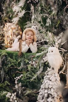 Hübsches kaukasisches kind mit langen blonden haaren liegt in der weihnachtsatmosphäre mit vielen geschmückten bäumen um sie und eule