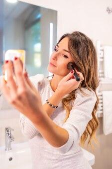 Hübsches kaukasisches mädchen, das sich im badezimmer schminkt und in den spiegel schaut, vertikales foto