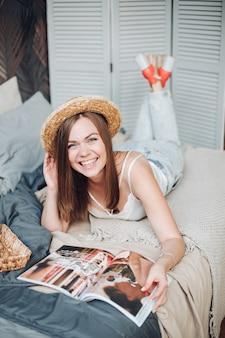 Hübsches kaukasisches mädchen mit dunklem lockigem haar, hut, weißem t-shirt, jeans liegt im großen hellen schlafzimmer und liest eine zeitschrift