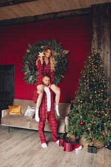 Hübsches kaukasisches paar, das in der gleichen nachtwäsche verliebt ist, schmückt weihnachtsbaum zusammen zu hause