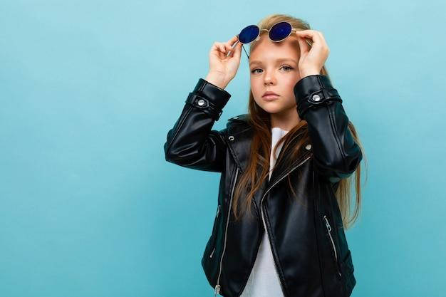 Hübsches kaukasisches teenager-mädchen mit langen braunen haaren in schwarzer jacke und jeans hält schwarze sonnenbrille lokalisiert auf blauem hintergrund
