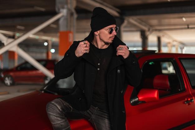 Hübsches kerlmodell mit sonnenbrille in modischer schwarzer kleidung mit mantel und hut in der nähe eines roten autos in der stadt