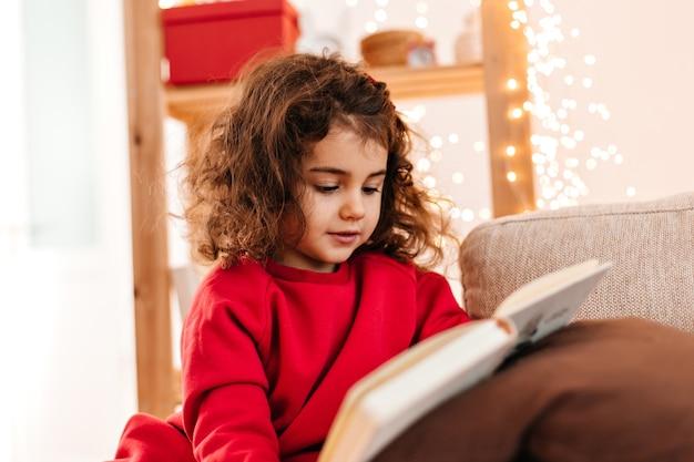 Hübsches kind, das buch zu hause liest. innenaufnahme des lockigen kleinen mädchens im roten hemd.