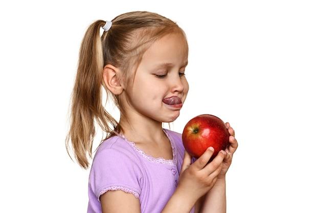 Hübsches kind isst roten apfel und streckt die zunge auf weißem hintergrund heraus