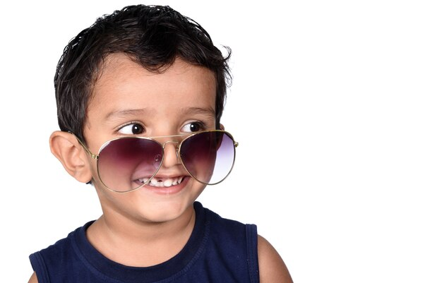 Hübsches kind mit sonnenbrille. schöner lächelnder kinderjunge in der sonnenbrille, die weiß lokalisiert auf weiß gestikuliert.