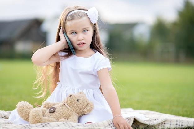 Hübsches kindermädchen, das im sommerpark auf grünem gras zusammen mit ihrem teddybärspielzeug spricht, das auf handy spricht, das glücklich draußen im sommer lächelt.