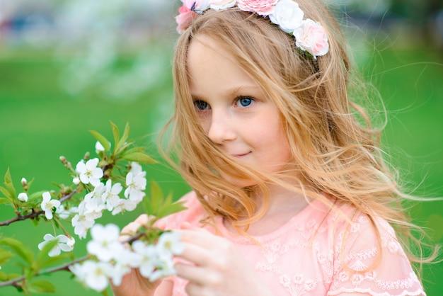 Hübsches kindermädchen, das lächelt und in blumen des gartens spielt, blühende bäume, kirsche, äpfel.