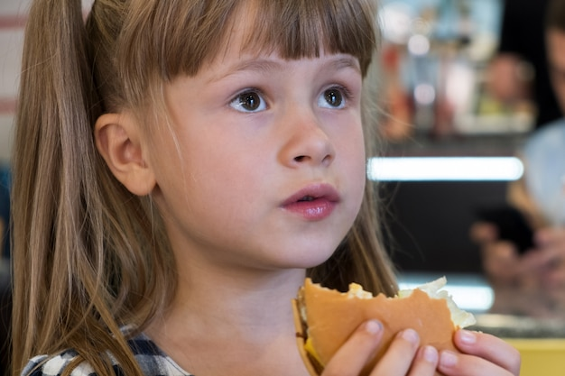 Hübsches kindermädchen, das schnellimbiß in einem restaurant isst.