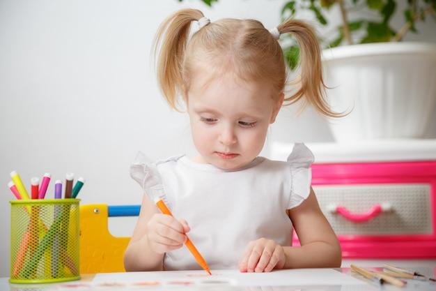 Hübsches kindermädchen, das zu hause mit aquarellen malt