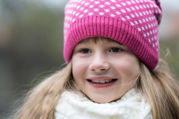 Hübsches kindermädchen im warmen gestrickten winter kleidet draußen.