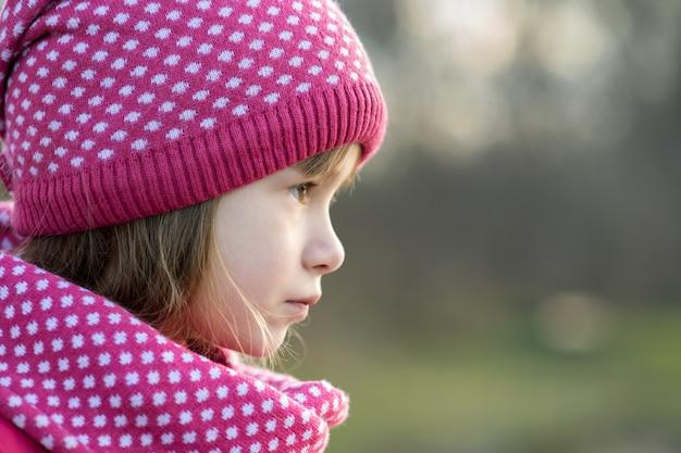 Hübsches kindermädchen in der warmen gestrickten winterkleidung draußen.
