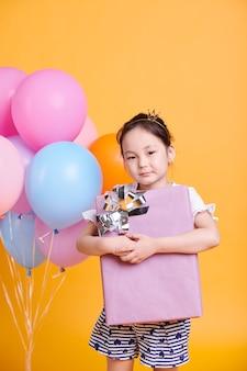 Hübsches kleines asiatisches mädchen mit großer verpackter geschenkbox, die isoliert auf gelber wand steht