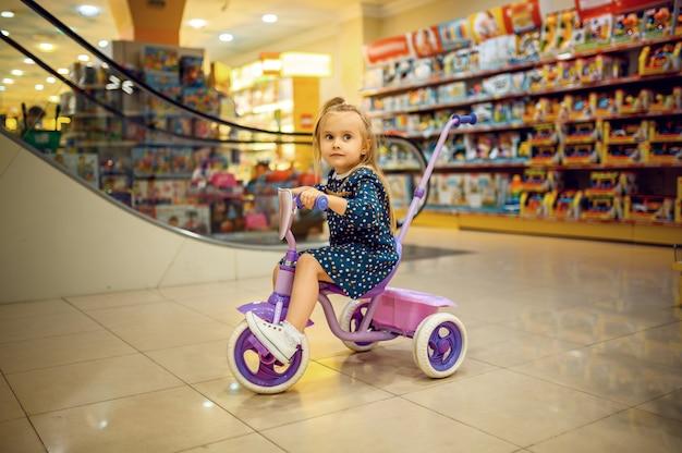 Hübsches kleines baby, das auf fahrrad im kindergeschäft reitet. entzückendes kind, das auf mutter im spielzeugladen wartet