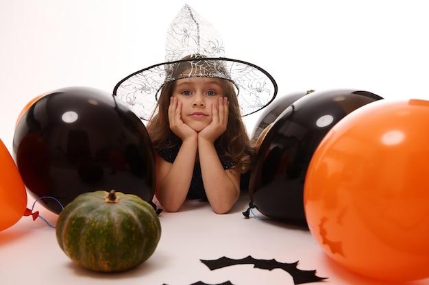 Hübsches kleines hexenmädchen in einem zauberhut, das auf einem weißen hintergrund mit kopienraum neben handgemachten filzschlägern, kürbis und orange schwarzen ballonen liegt. traditionelle veranstaltung, halloween-party-konzept.