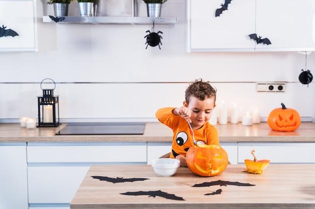 Hübsches kleines kind in einem halloween-kürbis-t-shirt gekleidet, das einen halloween-kürbis öffnet und entleert...