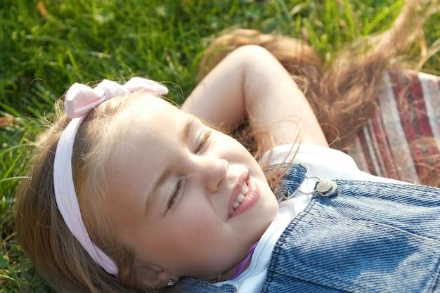 Hübsches kleines kindermädchen, das im sommer auf grünes gras legt und ein nickerchen macht.