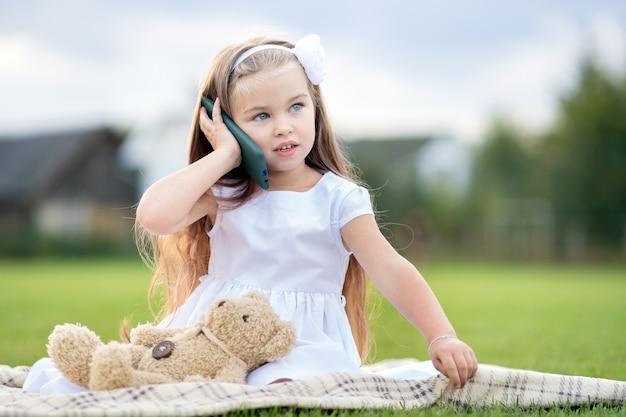 Hübsches kleines kindermädchen, das im sommerpark mit ihrem teddybärspielzeug sitzt und auf dem handy spricht