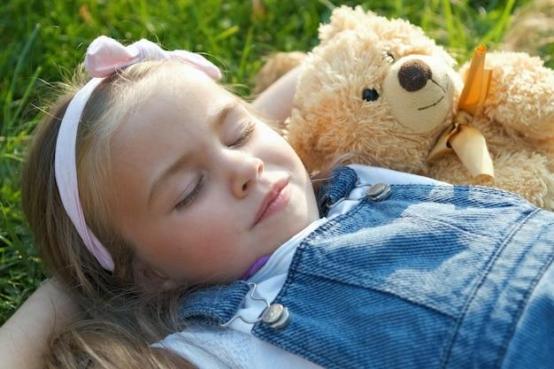 Hübsches kleines kindermädchen mit geschlossenen augen, die mit ihrem teddybärspielzeug auf decke auf grünem gras im sommer ein nickerchen machen.
