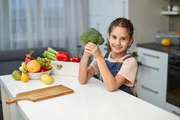 Hübsches kleines lächelndes lockiges mädchen mit brokkoli, das am tisch in der küche sitzt.